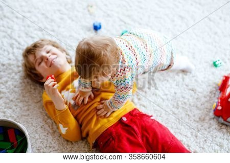 Happy Joyful Baby Girl Playing With Different Colorful Toys At Home. Adorable Healthy Toddler Child