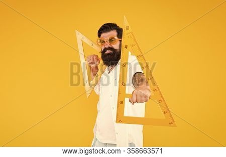 Math Genius. Geometry Geek Holding Triangles On Yellow Background. Geek Or Nerdy Student Making Angl