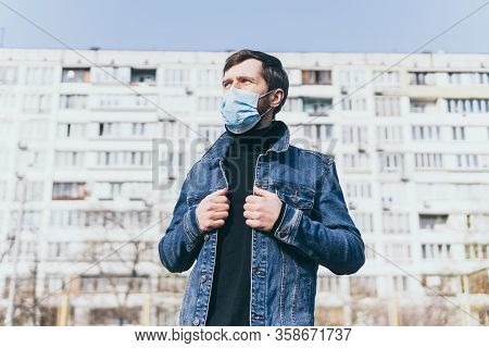 Concerned Young Man Wearing Medical Mask Outdoors With Residential Building On Background. Corona Vi