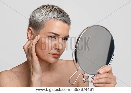 Skin Aging. Mature Woman Looking In The Mirror Checking Her Wrinkles, Sad About Face Imperfections,