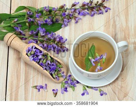 Sage Herbal Tea, Salvia Officinalis. Sage Leaves And Flowers On Wooden Board. Focused On Flowers In
