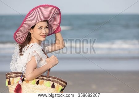 Woman Carry Big Handcraft Bag Wearing Beautiful Hat Standing And Looking To Camra With Wave And Back