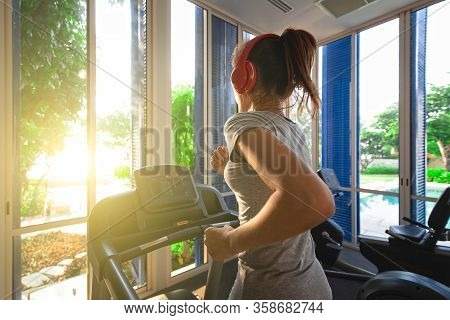 Good Shape Woman Running On Treadmill In Indoor Gym In Morning Light. Concept For Healthcare Of Mode