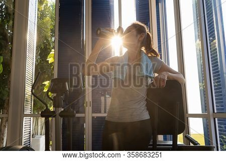 Woman In Sport Cloths Drinking Water From Bottle In Gym. There Is Sunlight Ray Of Moning In Backgrou