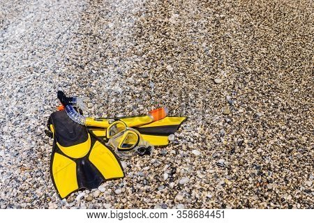 Snorkel Equipment Flippers And Snorkeling Mask Tube Lying On Stone Beach Sea Shore. Summer Vacation