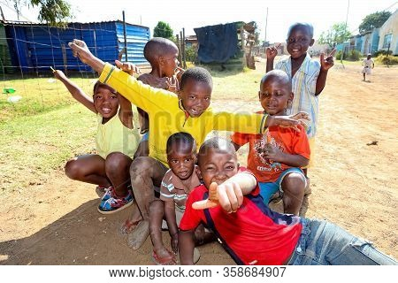 Small Group Of Young African Children Posing For A Photo And Displaying Friendship And Joy In A Sowe