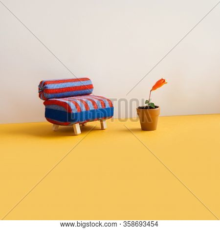 Blue Red Chair Toy Sofa And Berries Plant Flowerpot. Beige Wall, Yellow Floor Background. Copy Space