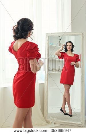 Young Brunette Woman Stands Looking In Reflection In A Full-length Mirror In A Short Red Dress In St