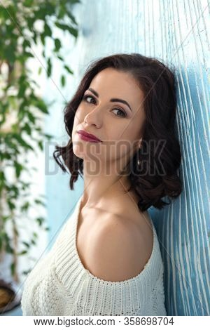 Portrait Of A Dreaming Attractive Stylish Woman In A White Sweater On One Shoulder Near The Blue Wal
