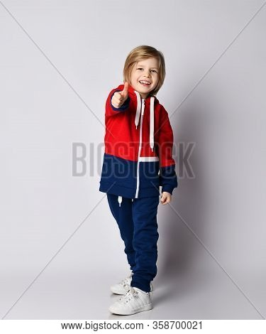 Frolic Happy Smiling Blond Kid Boy In Blue And Red Sportswear Hoodie And Trousers Is Showing Thumb U