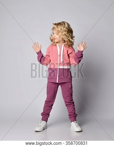 Beautiful Frolic Sly Smiling Curly Hair Blonde Kid Girl In Modern Fashion Pink Gray Sports Suit Hood