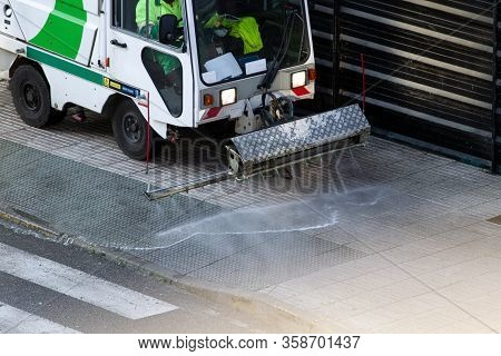 Street Cleaning Machine Working On A Sidewalk. Sweeper Cleaning The Sidewalk With Pressurized Water.