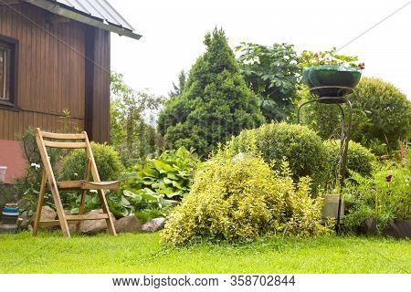 Beautiful Garden With Blooming Flower Beds, A Green Lawn And A Wooden Garden Chair Near Country Hous