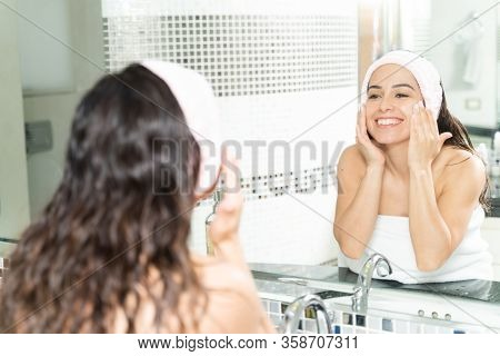 Portrait Of A Gorgeous Woman In Her 30s Wearing A Headband And Putting On Some Face Cream In The Bat