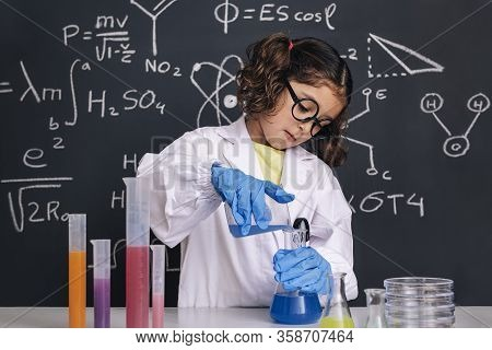 Little Scientist Kid With Glasses And Gloves In Lab Coat Mixing Chemical Liquids In Flasks, On Black
