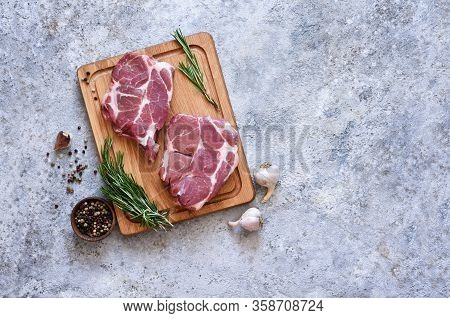 Striped Steak On A Wooden Board With Spices On A Concrete Plate. Ingredients For Cooking.
