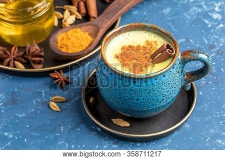 Blue Cup Of Traditional Indian Ayurvedic Golden Turmeric Latte Milk With Curcuma Powder, Cardamom, H