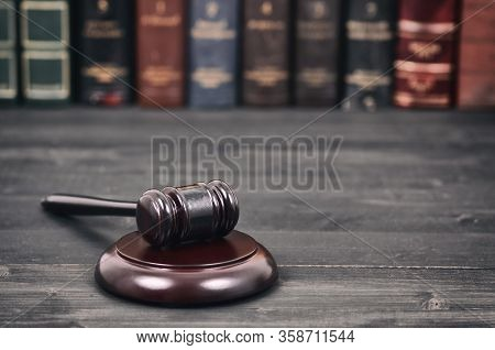 Law And Justice, Legality Concept, Judge Gavel On A Black Wooden Background In Front Of A Law Librar