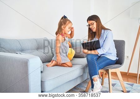 Young therapist woman speaking and treating child, counselor and behaviour correction at pedagogue payroom taking notes on clipboard