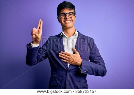 Young handsome business man wearing jacket and glasses over isolated purple background smiling swearing with hand on chest and fingers up, making a loyalty promise oath