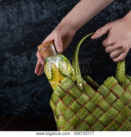 Female Hand Takes A Glass Bottle Of Clean, Cool And Fresh Drink From A Green Wicker Eco Ladies Bag O