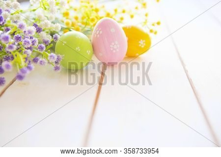 Easter Eggs And Bouquet Of Flowers On White Table Wood