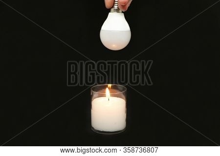 Innovation - Close-up, Candle And New Economical Light Bulbs On A Black Background.
