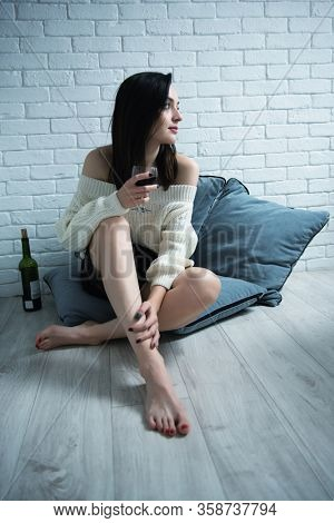 Portrait of charming young woman sitting on the floor at home and drinking red wine, image toned and noise added