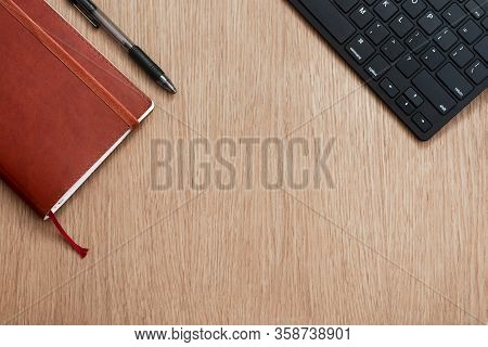 Brown Notebook, Black Pen And Computer Keyboard On A Wooden Surface. Business Concept. Business Peop