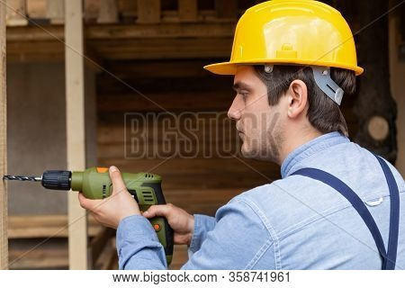 Young Handsome Carpenter With Yellow Hard Hat And Work Equipment Is Holding An Electric Drill On Woo