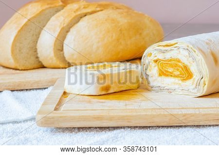 Sliced Roll Of Armenian Pita Bread With Carrot Filling On A Wooden Board. On The Board Are Cloves Of
