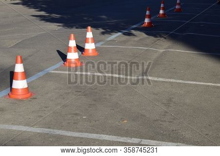 The Sunlight On Parking Cone On The Monochrome Background. Plastic Orange Parking Cone Standing In T