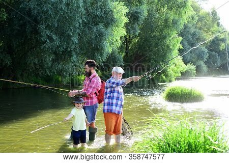 Little Boy Fly Fishing On A Lake With His Father And Grandfather. Man With His Son And Father On Riv