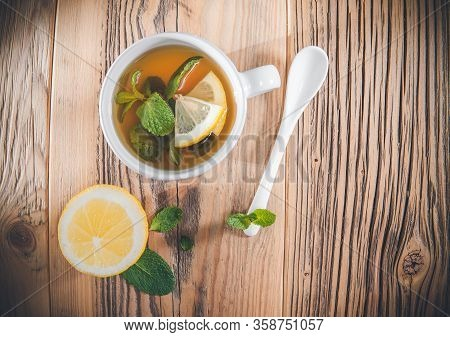 Mint Tea Leaves In A Cup With Fresh Slice Lemon On Wooden Table.