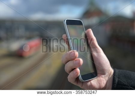 Hand Of A Man With A Mobile Phone, Station, Railroad Tracks And Train Blurred In The Background, Con