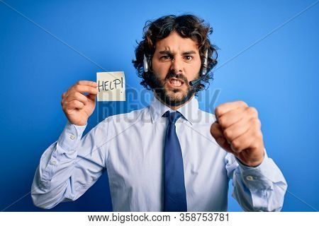Young handsome call center agent man with beard working using headset holding help reminder annoyed and frustrated shouting with anger, crazy and yelling with raised hand, anger concept