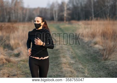 Young Slim Active Woman In Total Black Sportswear Is Jogging In The Countryside. She Is In A Protect