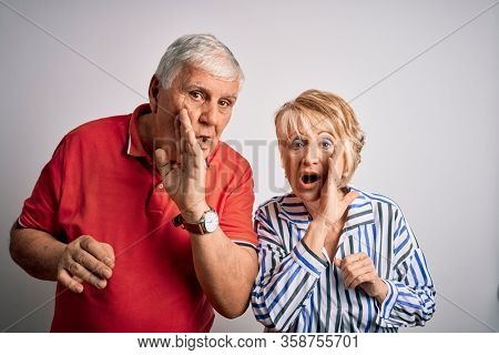 Senior beautiful couple standing together over isolated white background hand on mouth telling secret rumor, whispering malicious talk conversation