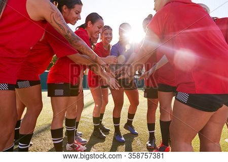 Manager Joining Hands With Womens Soccer Team During Pep Talk Before Match