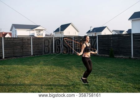 Sport Lifestyle, Healthy Lifestyle. Cardio Workout In The Backyard. A Young Girl In Sportswear Is Pl