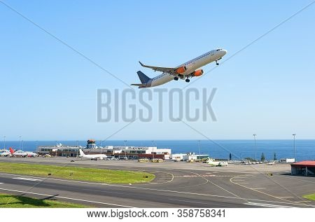 Airplaine Taking Off Runway At Madeira International Airport, Terminal Building And Seascape In Back