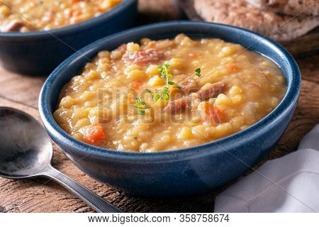 A Bowl Of Delicious Yellow Split Pea Soup With Carrots And Smoked Ham.