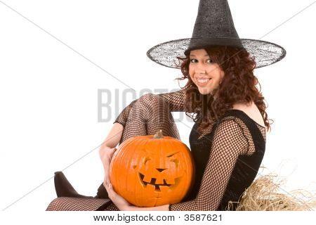 Teen Girl In Halloween Costume With Pumpkin