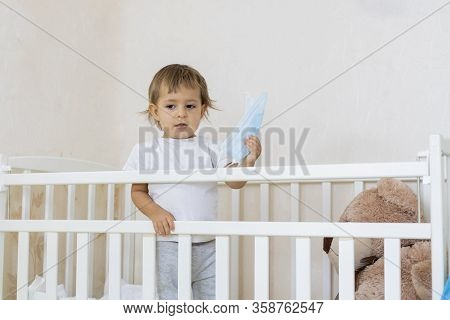 Quarantine Coronavirus Covid-19 Pandemic Concept. A Little Cute Serious Baby Is In A Baby Cot At Hom