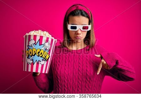 Young beautiful girl watching movie using 3d glasses eating box with popcorns Pointing down looking sad and upset, indicating direction with fingers, unhappy and depressed.