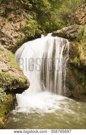 A Rapid Mountain Stream Of Water Forms A Large Waterfall. The Stream Of Water Rushes From The Mounta