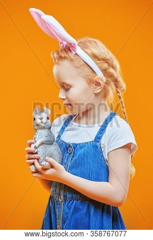 Cute redhead little girl poses in a t-shirt and denim sundress with bunny ears and holding a rabbit toy in his hands over yellow background. Children's fashion and beauty. Easter holiday.