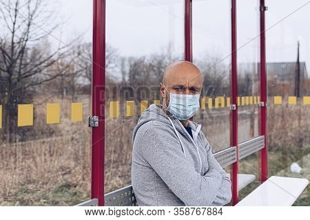 Caucasian Man In Protective Medical Mask Waiting For A Bus On City Bus Stop. Public Transport