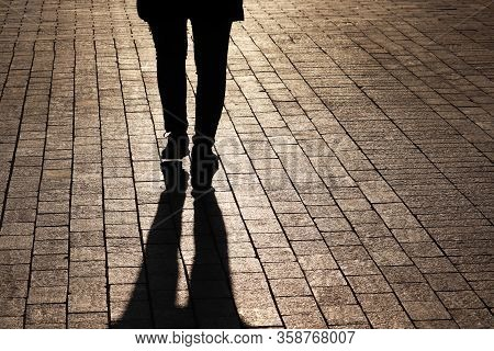 Silhouette And Shadow Of Lonely Woman Walking On A Street. Female Legs On A Sidewalk, Concept Of Lon