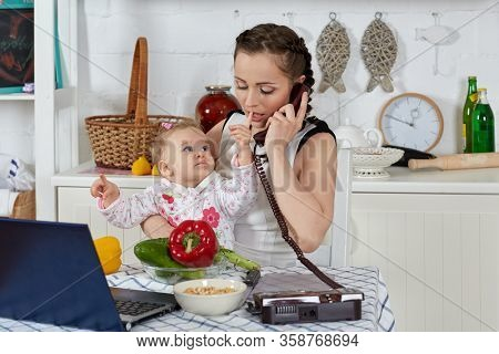 Mother with notebook and little child sit at dining table in home kitchen. Isolation period, quarantine, social distancing. Remote education or remote work